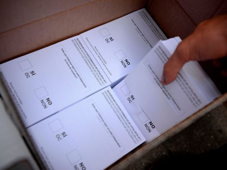 A Pro-referendum demonstrator grabs a pack of ballots before their distribution to passer-by during a demonstration