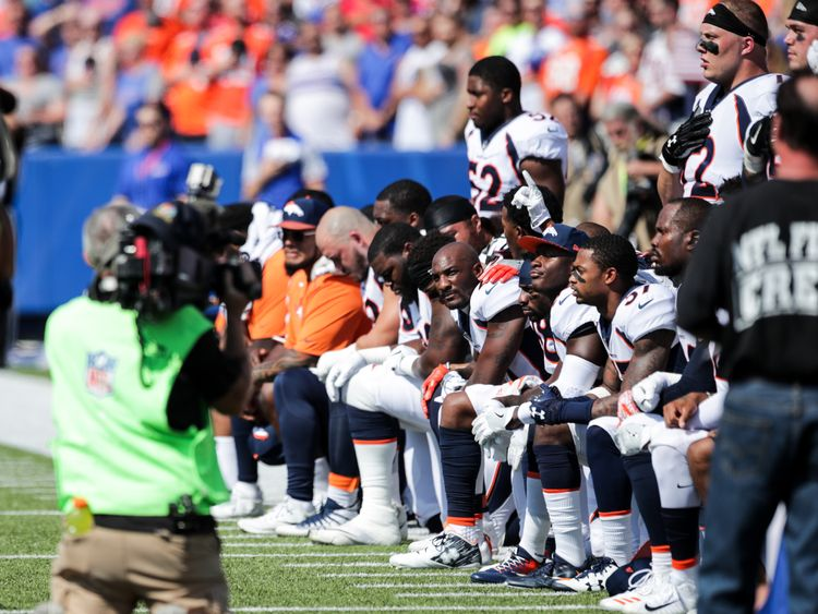 Denver Broncos players kneel during the American National Anthem before an NFL game against the Buffalo Bills