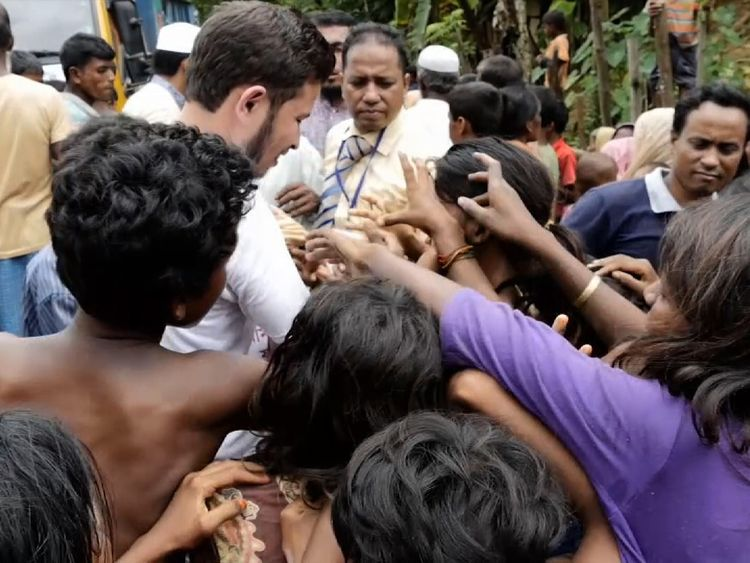 Aid worker hands out food to Rohingyas