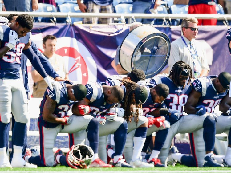 Members of the New England Patriots kneel on the sidelines as the National Anthem is played before a game against the Houston Texans at Gillette Stadium