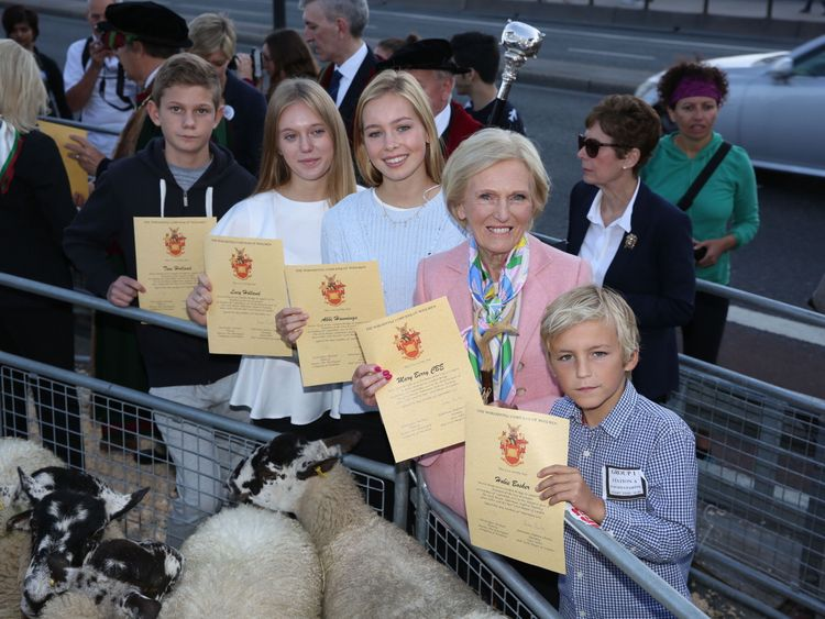 Celebrity baker Mary Berry holds her certificate with participants after herding sheep over London Bridge to help open the Wool Fair