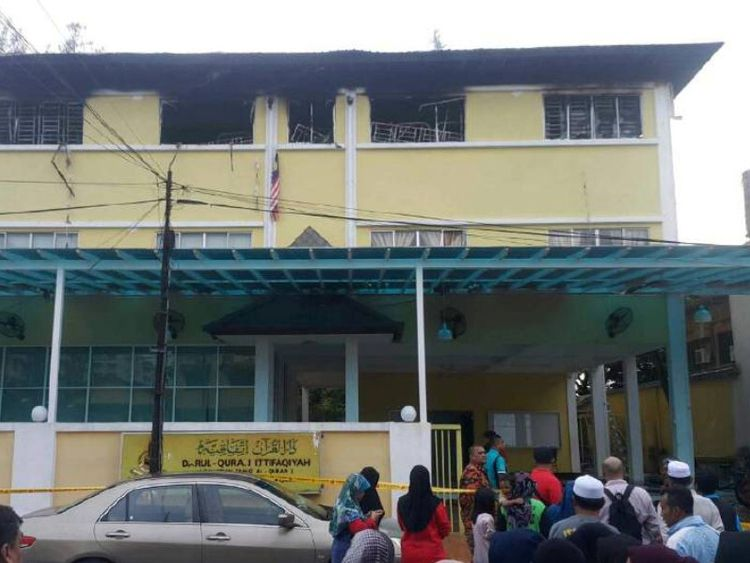 People gather outside the religious school Darul Quran Ittifaqiyah after a fire broke out in Kuala Lumpur