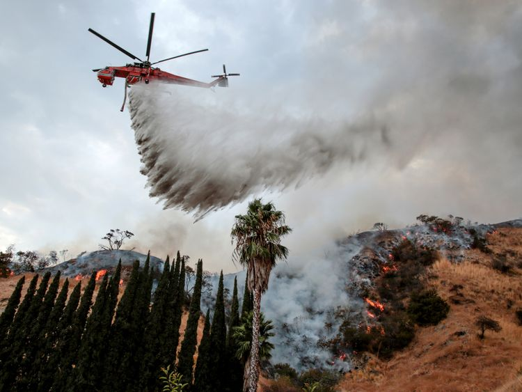 A helicopter drops water over Burbank, California