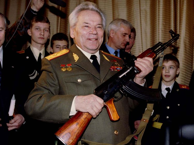 Mikhail Kalashnikov, pictured in 1997, holds aloft an AK-47