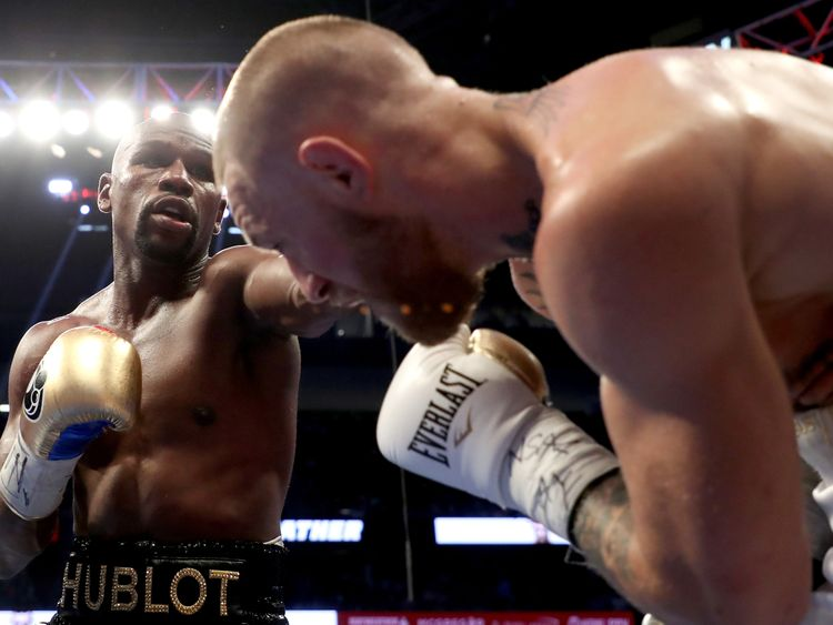 LAS VEGAS, NV - AUGUST 26:  (L-R) Floyd Mayweather Jr. throws a punch at Conor McGregor during their super welterweight boxing match on August 26, 2017 at