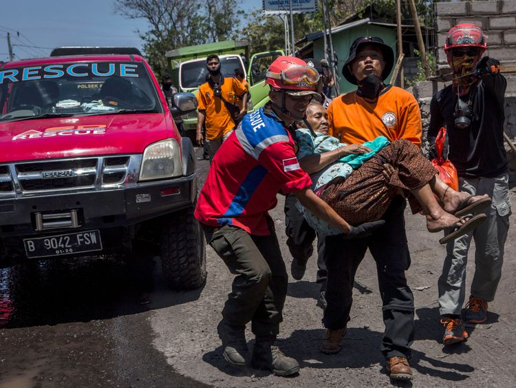 An elderly woman is evacuated from her village by rescue workers