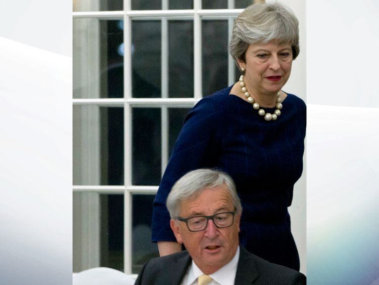 Theresa May walks past European Commission President Jean-Claude Juncker