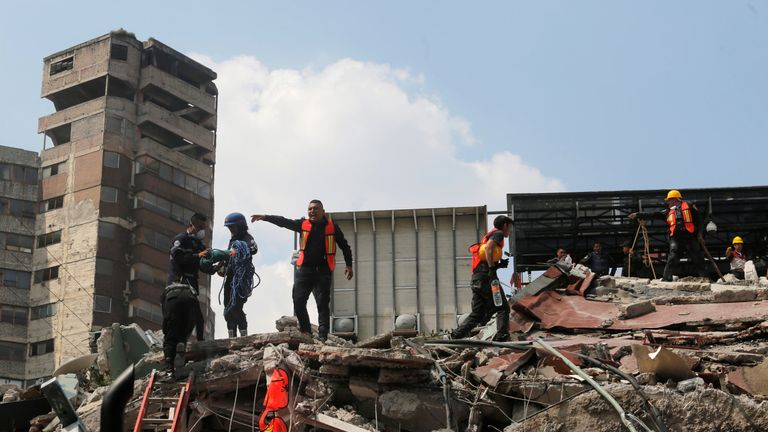 Rescue personnel stand on top of the rubble of a collapsed building while searching for people