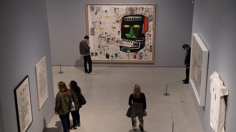 People look at a painting titled 'Glenn' by US artist Jean Michel Basquiat