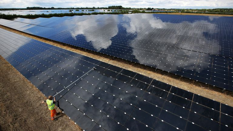 A workman cleans panels at Landmead solar farm near Abingdon