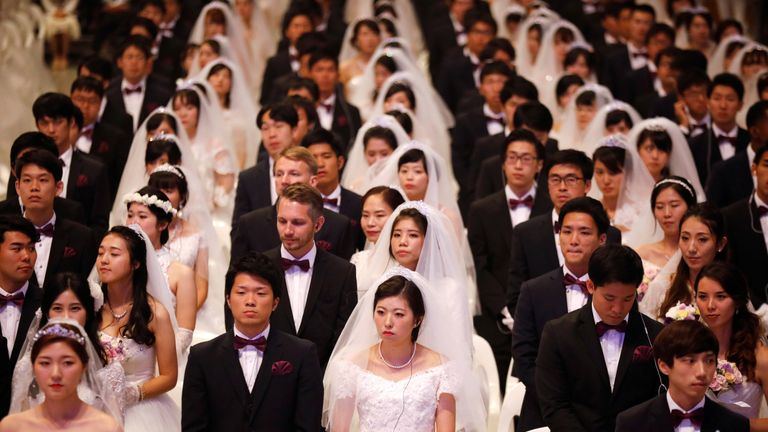 Newlywed couples attend a mass wedding ceremony of the Unification Church
