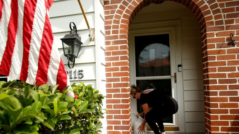 A woman in Florida sets out sandbags to protect her house from the storm