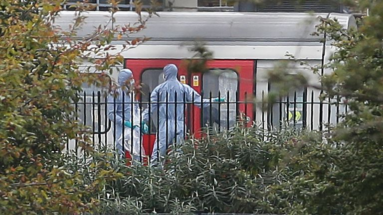 Police forensics officers works alongside an underground tube train at a platform at Parsons Green