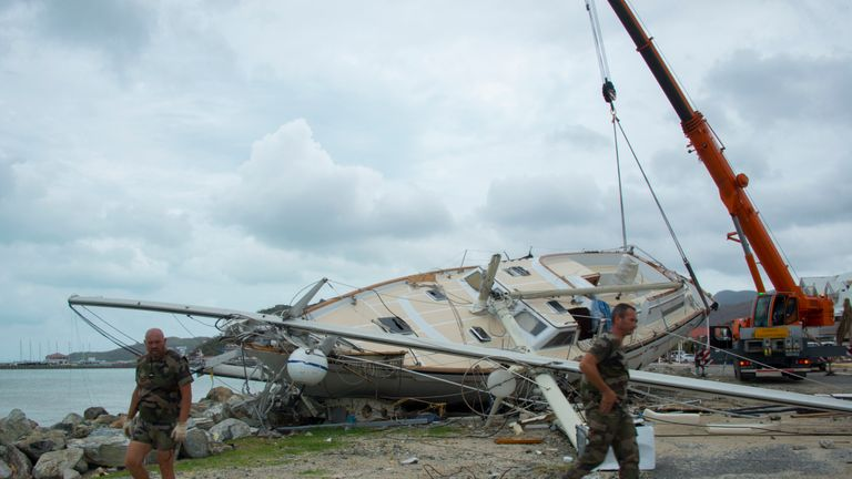 Members of the military help remove damaged boats in Orient Bay, St. Martin