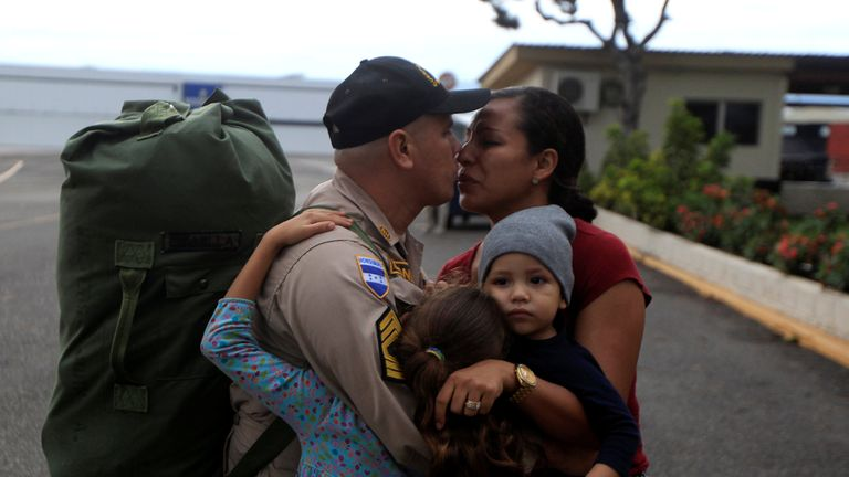 A rescue member of the Permanent Contingency Commission of Honduras (COPECO) bids farewell to his family while departing for Mexico