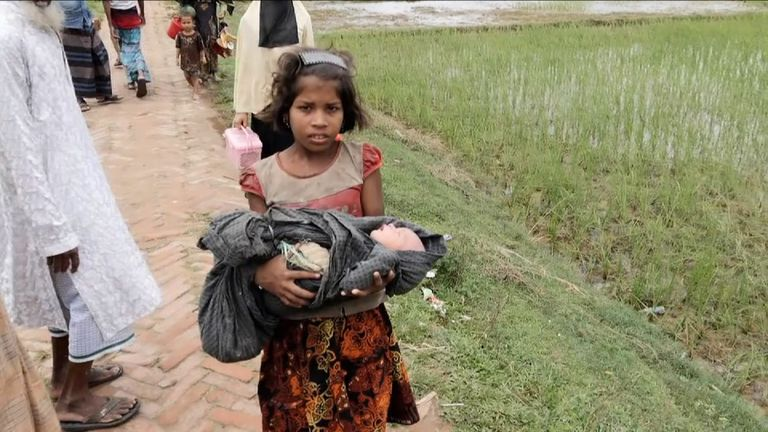 A young girl carries her five-day-old brother