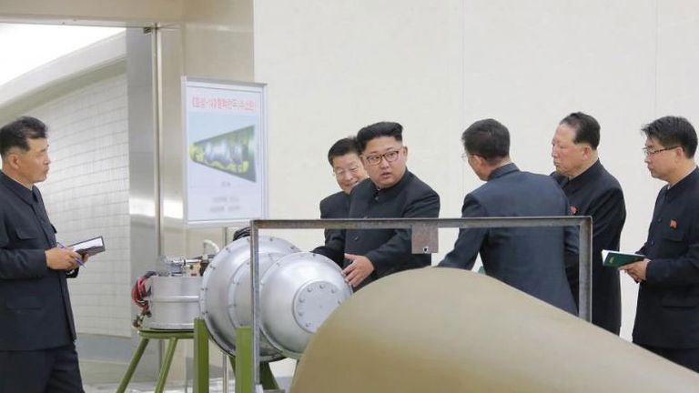 Kim looking at purported weapon at Pyongyang's Nuclear Weapons Institute