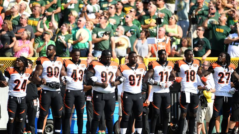 The Cincinnati Bengals stand with arms locked as a sign of prior to their game against the Green Bay Packers