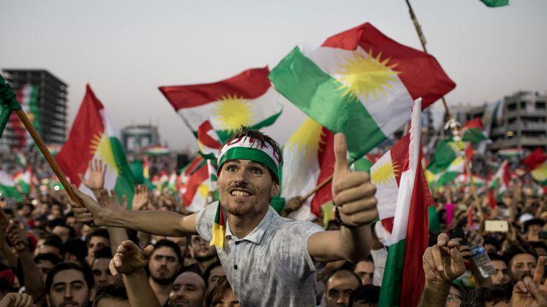 Supporters wave flags and chant slogans inside the Erbil Stadium while waiting to hear Kurdish President Masoud Barzani