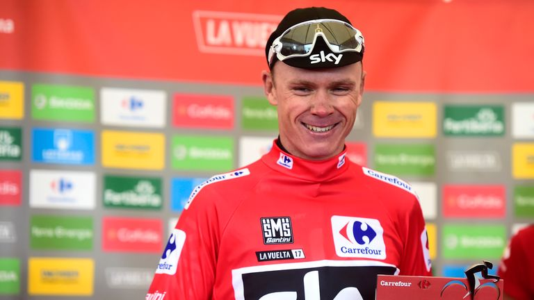 Sky's British cyclist Chris Froome smiles as he sports the overall leader's red jersey  on 9 September