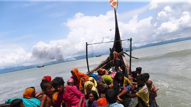 Smoke is seen on Myanmar's side of border as Rohingya refugees get off a boat after crossing the Bangladesh-Myanmar border through the Bay of Bengal