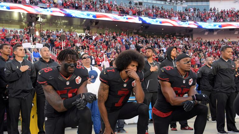Colin Kaepernick (C), Eric Reid (R) and Eli Harold (L) kneel in protest during the national anthem in October 2016
