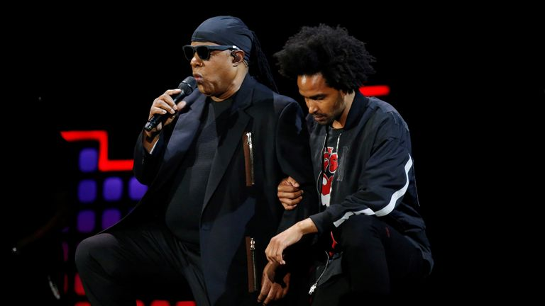 Stevie Wonder knelt with his son Kwame Wonder while performing in New York