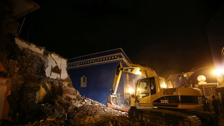 A machine works on a destroyed hotel