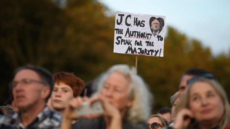 A supporter holds up a placard as they listen to Jeremy Corbyn at a Momentum rally