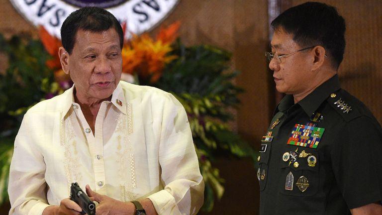 Philippine President Rodrigo Duterte (L) holds a handgun as military chief Eduardo Ano (R) looks on in July 2017