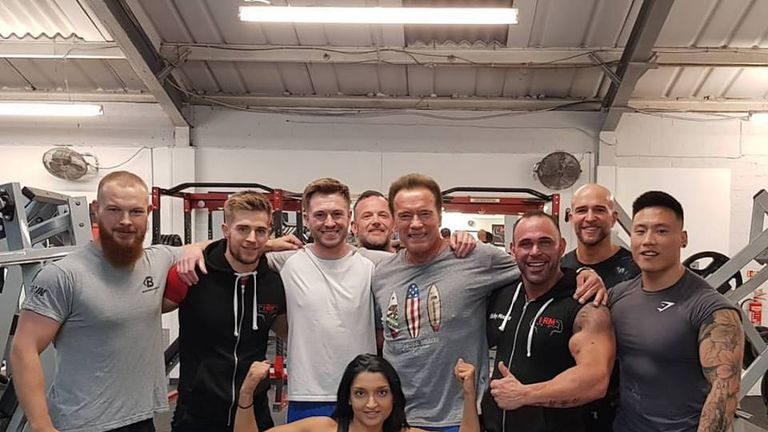 Arnold Schwarzenegger poses for a photo with the staff on duty during the hour he pumped iron. Credit Ricky Moore.