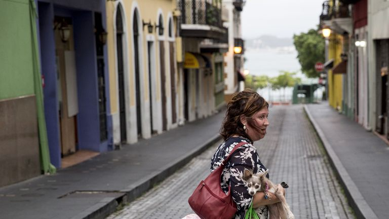 A woman and her dog leave their home in boarded up San Juan street before Hurricane Maria hits