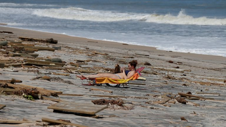 A woman sunbathes amongst debris on the beach after Hurricane Irma passed the area in Ponte Vedra Beach, Florida