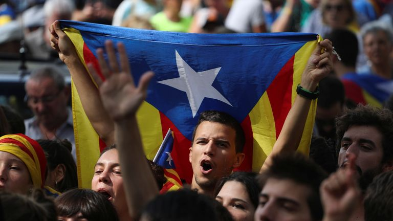 Protesters shout slogans and wave Esteladas (Catalan separatist flags) as they gather outside the High Court of Justice of Catalonia in Barcelona