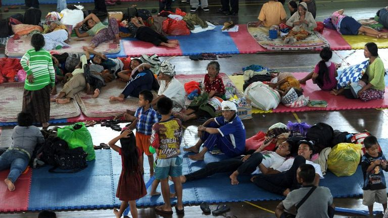 Villagers rest after being evacuated during the raised alert levels for the volcano on Mount Agung