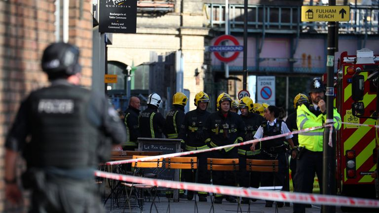 Members of the London Fire Brigade stand by cordon near Parsons Green tube station