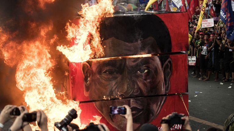 Activists burn an effigy during a protest against Rodrigo Duterte in Manila