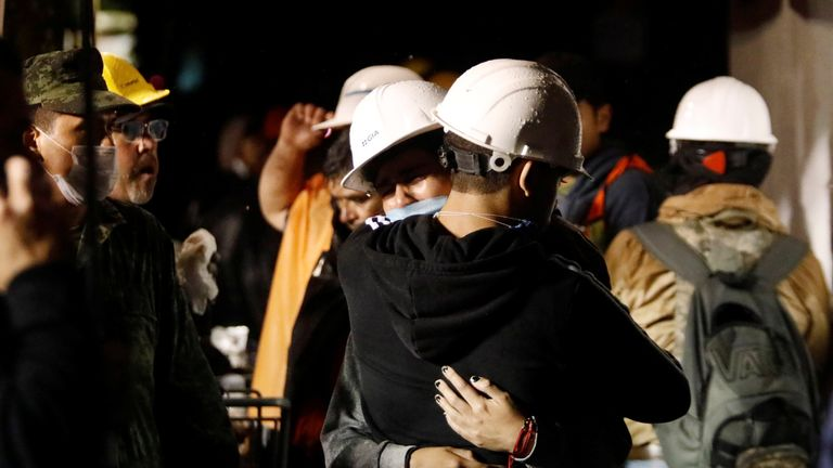 Workers hug during the search for students at Enrique Rebsamen school