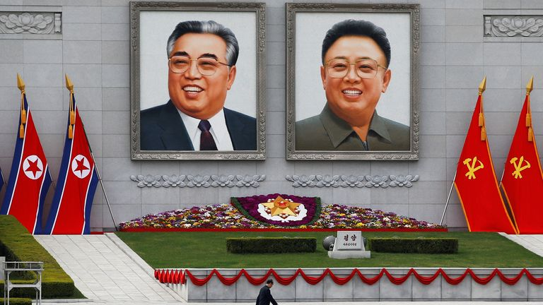 A man walks in front of portraits of North Korea founder Kim Il Sung and late leader Kim Jong Il in central Pyongyang, North Korea April 16, 2017