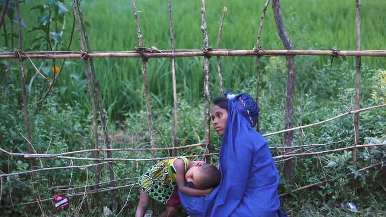 An exhausted Rohingya refugee rests with her daughter after jostling for aid outside a camp in Cox's Bazar, Bangladesh