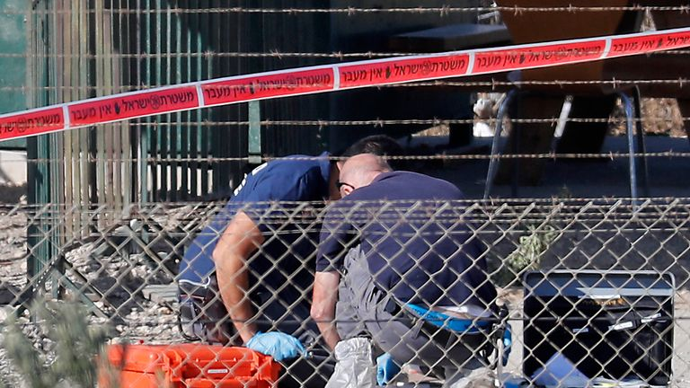 Forensics officers gather evidence at the site of the attack at the entrance to the West Bank settlement Har Adar