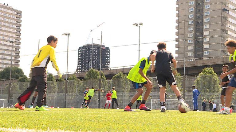 Children play football near the Grenfell Tower