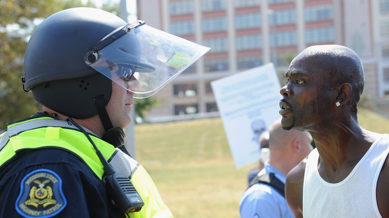A protester and a police officer face off following the acquittal of Jason Stockley