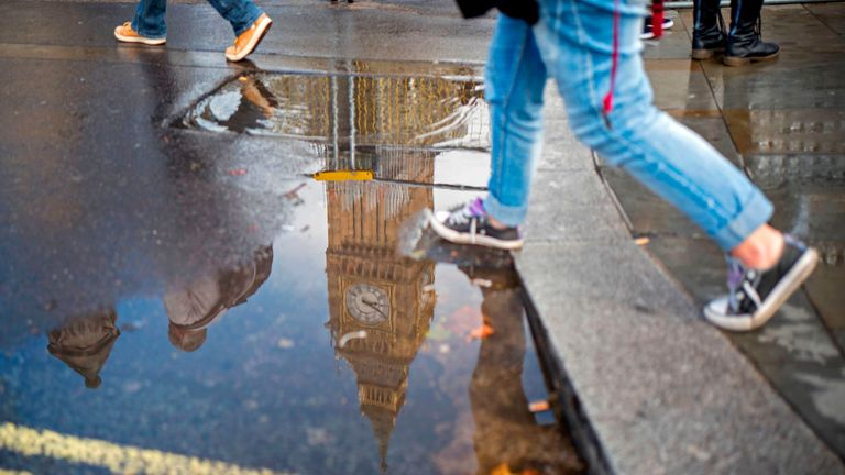 Big Ben is reflected in a puddle after a shower, in central London