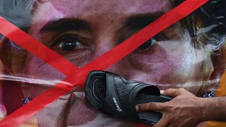 A Rohingya refugee living in Malaysia uses a slipper to hit a picture of Aung San Suu Kyi