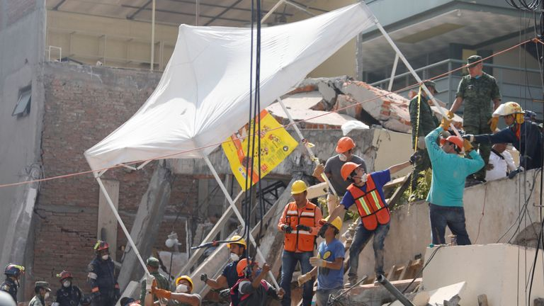 Rescue workers transport a tent as they search for students through the rubble at Enrique Rebsamen school