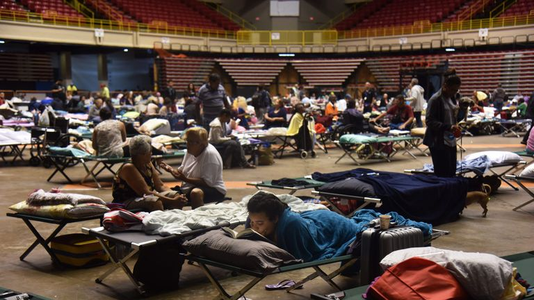 People have been sleeping on camp beds put up in sports halls in Puerto Rico