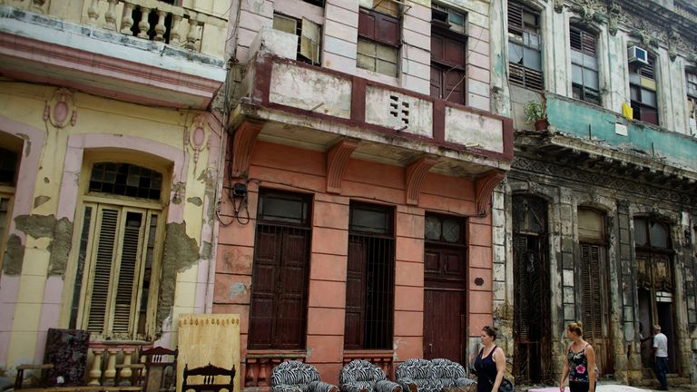 Tourists walk past furniture let to dry on the street after Hurricane Irma caused flooding and a blackout, in Havana, Cuba