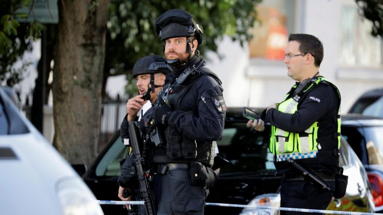 Armed policemen stand by cordon outside Parsons Green tube station in London, Britain