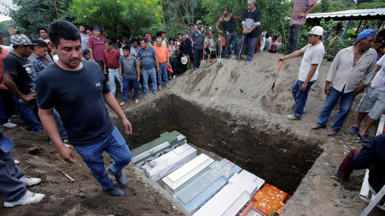 Caskets, holding the bodies of victims who died in an earthquake, are arranged in a grave, in Atzala, on the outskirts of Puebla